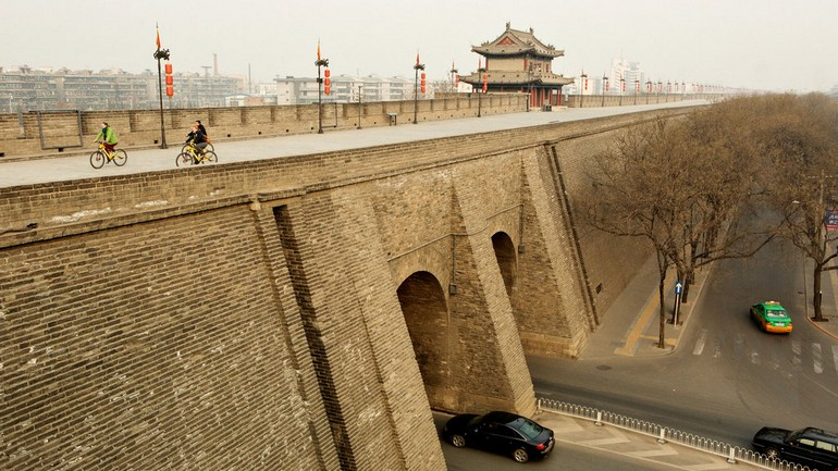 游客在西安城墙上骑车。Cyclists ride along a stretch of the city walls in Xian, China..jpg